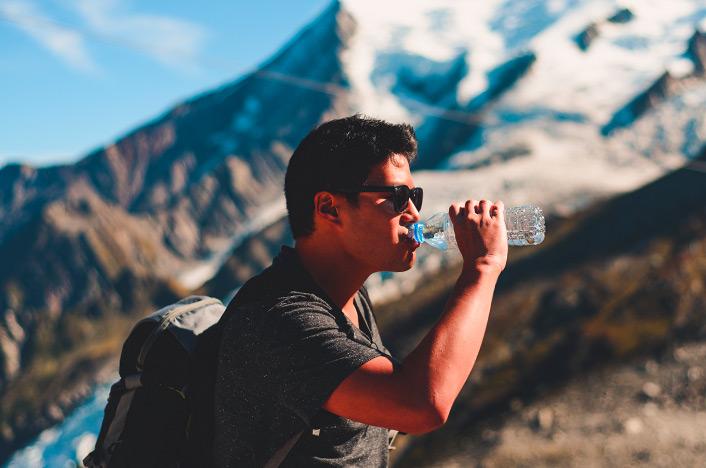 Hombre bebiendo agua en la montaña