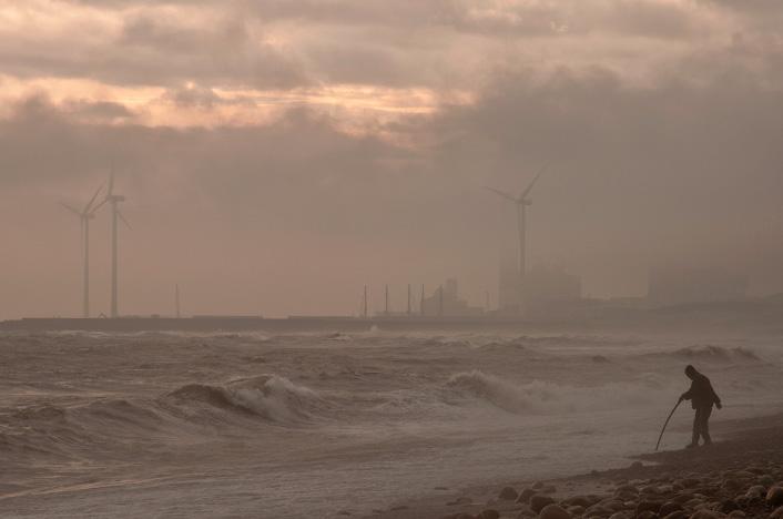 Playa contaminada con molinos de viento al fondo