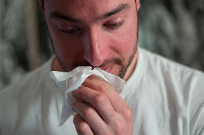 Hombre resfriado con pañuelo en la mano