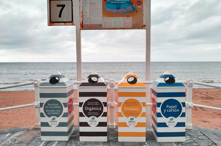 Cubos de reciclaje en la playa con tiempo nublado