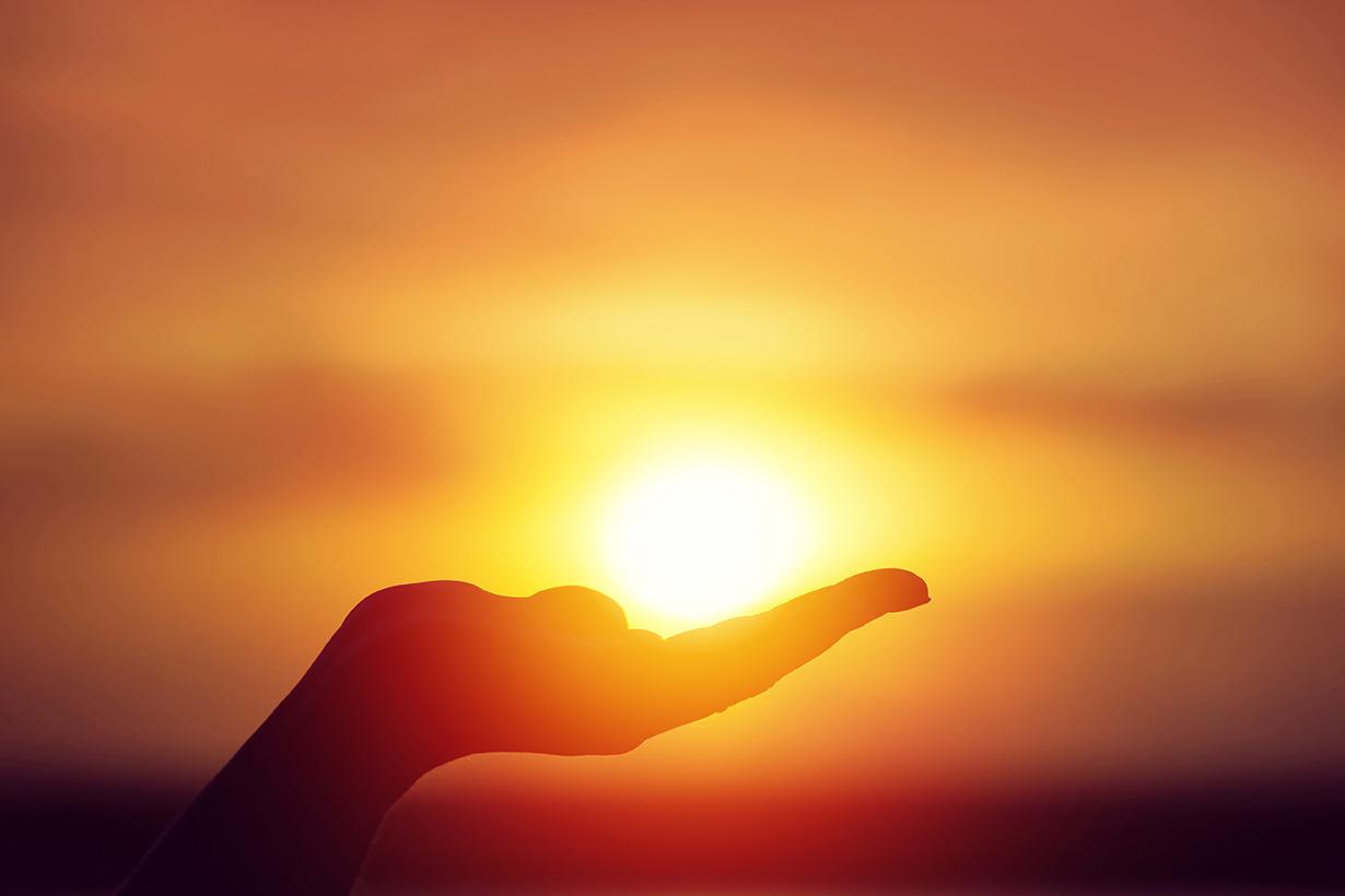 Mano sosteniendo el sol de fondo
