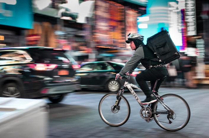 Repartidor usando bicicleta en la ciudad