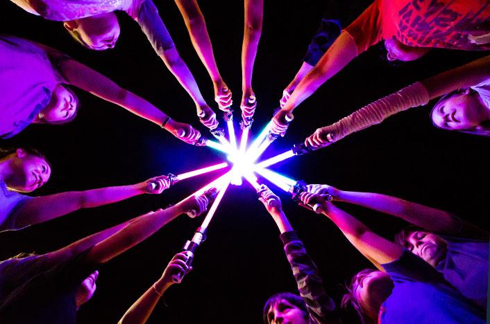 Almacenamiento de Energía. Gente sujetando barillas de luz.