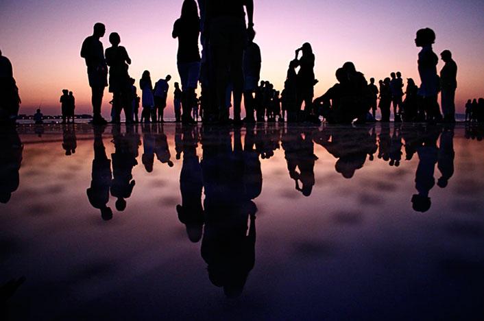 La ecología de poblaciones es importante para conocer la biodiversidad de las diferentes especies. En la imagen se muestran las siluetas de unas personas en la playa, al atardecer.