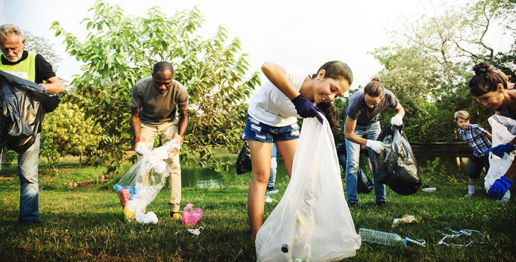 Personas limpiando un parque de plásticos y otros residuos con símbolo para reciclar