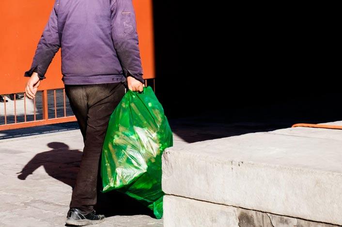 Hombre llevando bolsa de basura