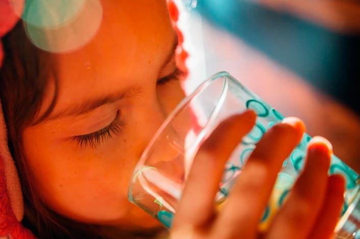 Niña bebiendo agua proveniente de humedales de Colombia