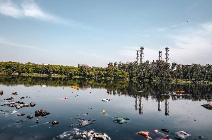 Lago contaminado con fábrica al fondo - Contaminación acuática