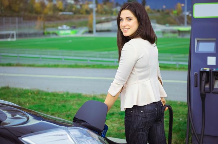 chica cargando coche eléctrico