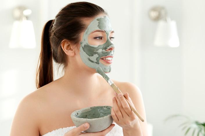 mujer aplicándose mascarilla facial