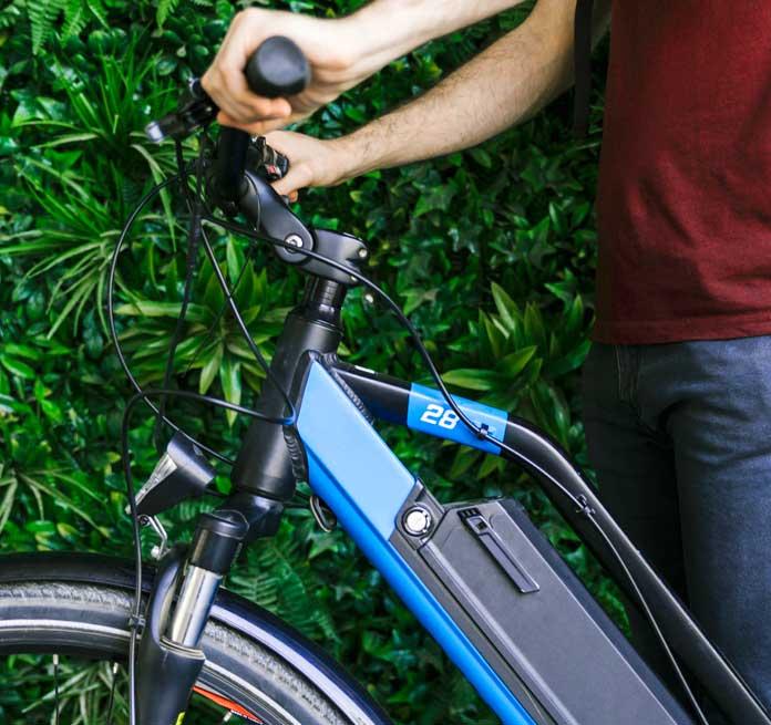 chico sosteniendo una bicicleta eléctrica