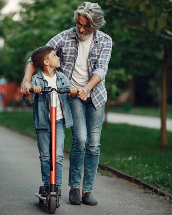 niño y abuelo con patinete eléctrico