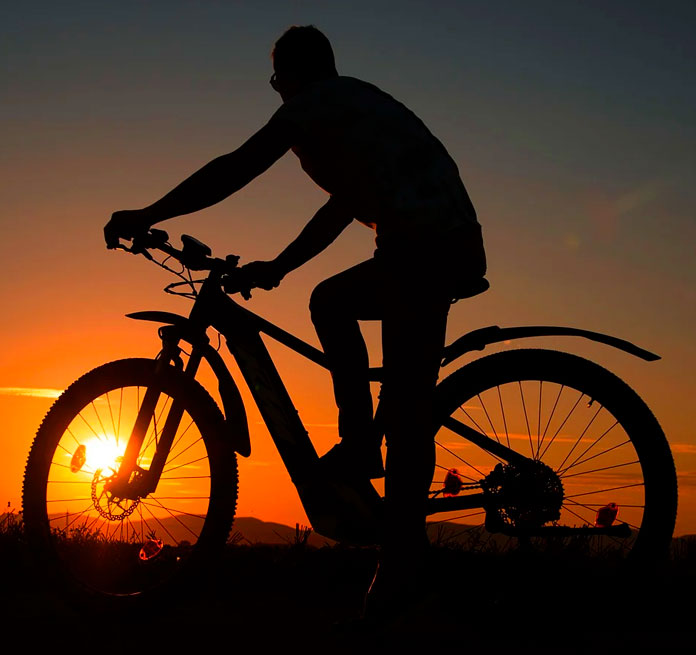 silueta de persona sobre bicicleta eléctrica