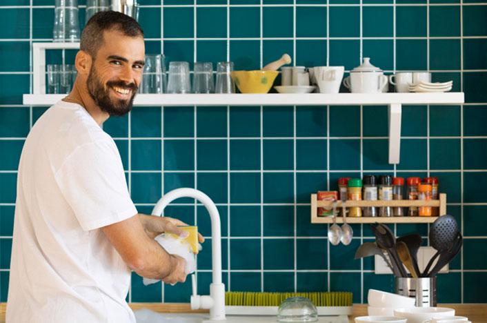 hombre lavando platos en casa
